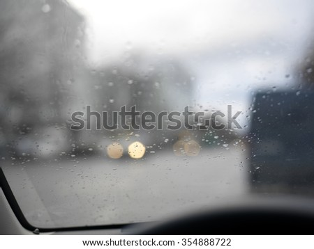 Close up of raindrops on a car windscreen, daytime shot with blurred background - stock photo