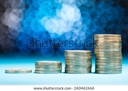 Close-up Of Raising Stack Of Coins With Bokeh Background