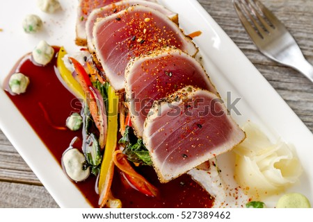 Close up of rare seared Ahi tuna slices with bok choy stir fry vegetables and wasabi peas on white plate with fork on side