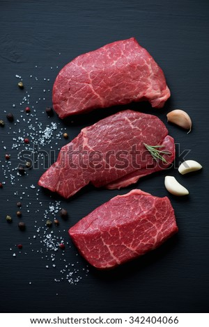 Close-up of raw fresh black angus beef with seasonings. Black wooden background, above view - stock photo