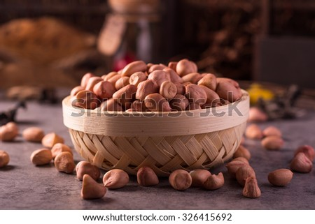 close up of raw peanuts or arachis in ceramic bowl on wood background - stock photo