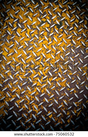 Close up of real diamond plate material with a slight vignette.  Most of the yellow paint is chipped and scratched off. - stock photo