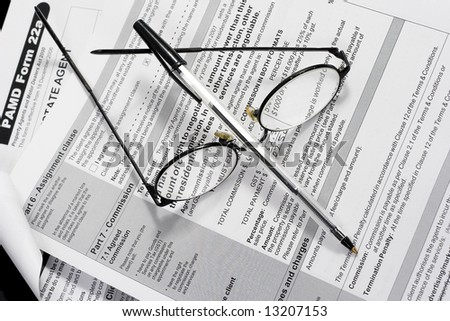 Close up of Real Estate contract with reading glasses and pen