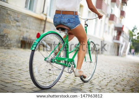 Close-up of rear view of a pretty woman on bicycle  - stock photo
