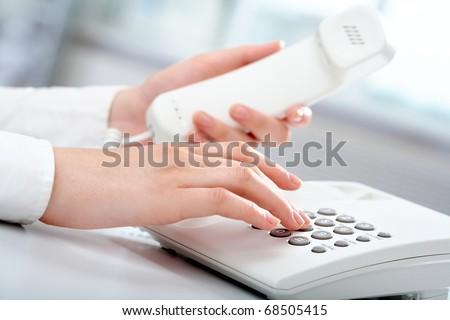 Close-up of receptionist making a phone call - stock photo