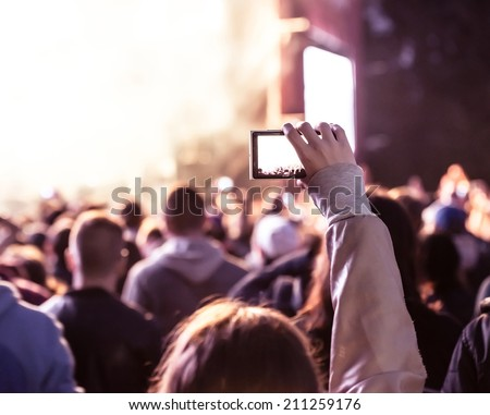 Close up of recording video with smartphone during a concert. Toned picture - stock photo