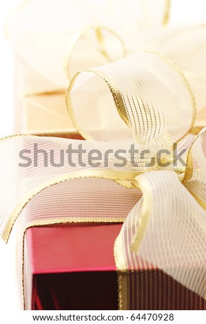 Close-up of red and gold foil gifts with golden bows on white background. - stock photo