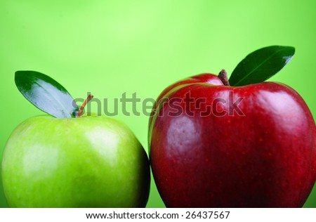 Close up of red and green apple on green background