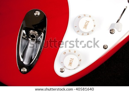 Close-up of red and white guitar body, knobs and plug - stock photo