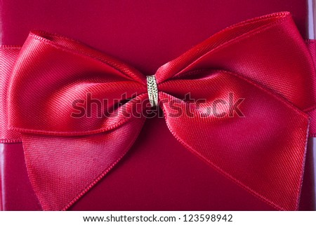 Close-up of red bow on red gift box. - stock photo