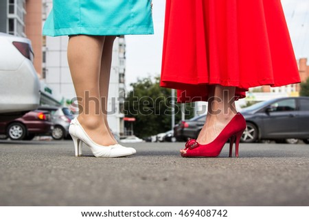 Close-up of Red classic shoes of a young girl in a long dress in front of the turquoise office shoes and a short dress woman against city street with the car