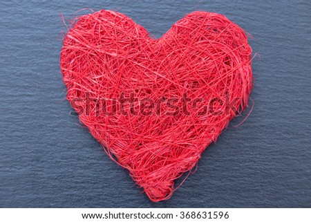 Close-up of red decorative heart made of yarn on grey background, isolated - stock photo