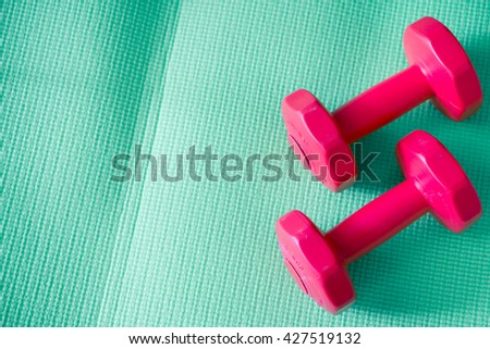 Close up of red dumbbell exercise weights on the green yoga mat at fitness gym.Red dumbbells. - stock photo