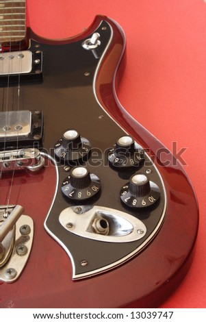 Close up of red electric guitar on red background - stock photo