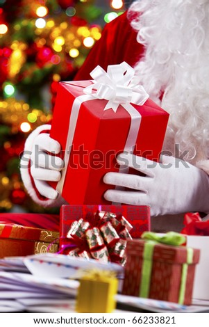 Close-up of red giftbox in Santa hands - stock photo