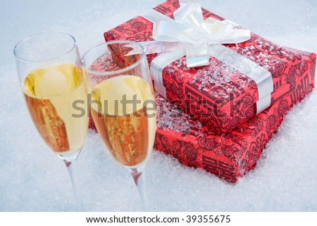 Close-up of red giftboxes with two flutes of champagne near by - stock photo