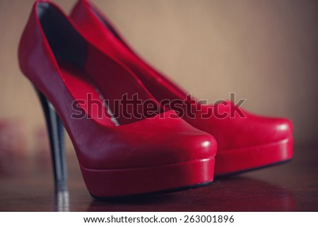 Close up of red high heel shoes are ready for wedding, stays on the brown table - stock photo