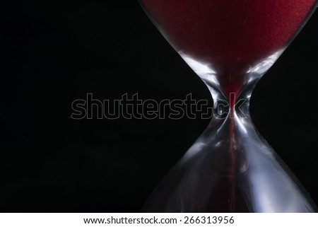 Close up of red hourglass on black background - stock photo