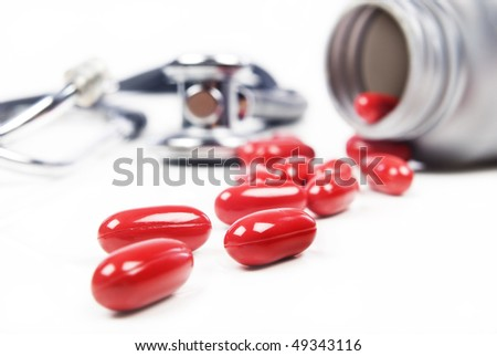 Close up of red pills with doctor's stethoscope and pill bottle - shallow depth of field