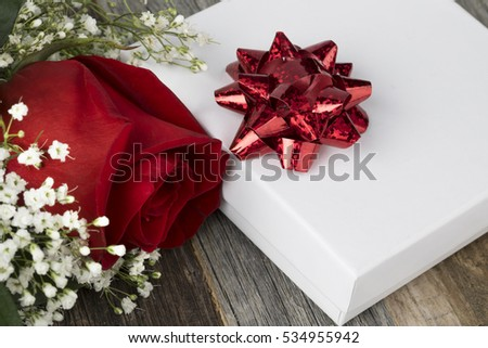 Close up of red rose and gift with red ribbon.