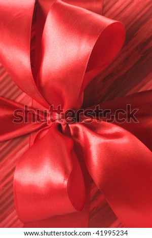Close-up of red satin bow on red striped wrapping paper. - stock photo