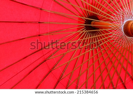 Close up of red umbrellas with wooden handle at Bo Sang Umbrella Village, Chiang Mai Mai, Thailand  - stock photo