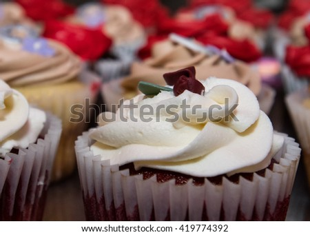 Close up of Red velvet cupcake with a variety of cupcakes in the background - stock photo