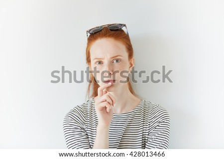Close up of redhead young woman with freckles wearing sailor shirt looking at the camera with serious and concentrated expression trying to remember something very important, with a finger on her chin - stock photo