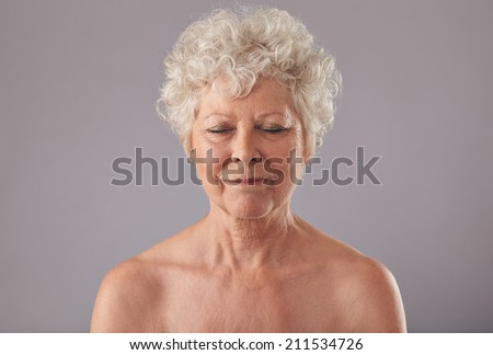 Close-up of relaxed old woman on grey background with her eyes closed in thought. Naked senior female against grey background. - stock photo