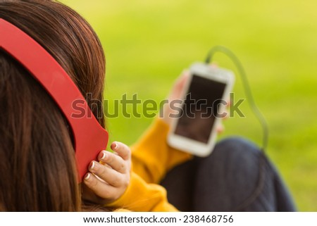 Close up of relaxed young woman enjoying music in the park - stock photo