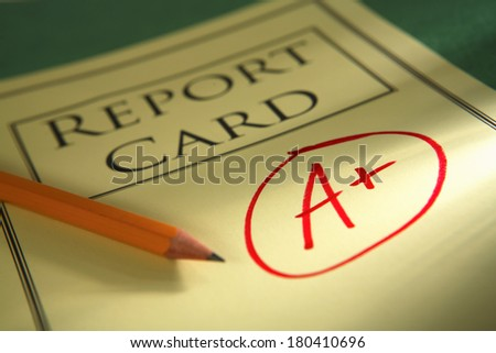 close up of report card with A+ and pencil  - stock photo