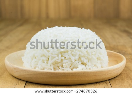close up of rice in wooden dish on wood  table. - stock photo