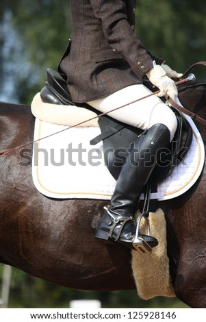 Close up of rider on horse during dressage competition - stock photo