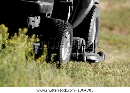 Close-up of Riding Lawnmower cutting a field (lawnmower is black and white while field is in color, mid-focus point on the mower deck). - stock photo