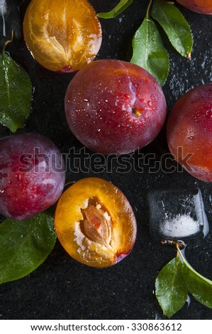 Close up of ripe plums with leaves on wet black stone background - stock photo