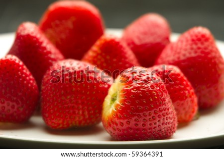 Close up of ripe strawberries on white plate. - stock photo