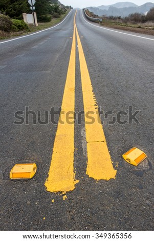 Close up of road reflectors and double yellow lines on a road going up a hill - stock photo