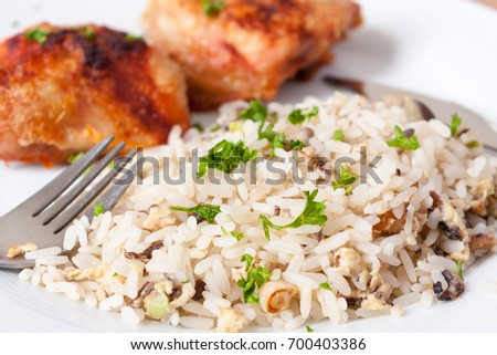 Close-up of roasted chicken thighs and mushroom rice on a white plate