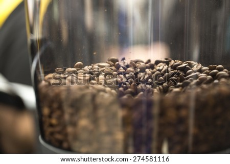 Close up of roasted coffee beans in a grinder, shallow depth of field - stock photo