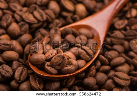 close up of roasted coffee beans in spoon on white table