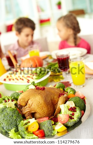 Close-up of roasted turkey served with broccoli on background of siblings - stock photo