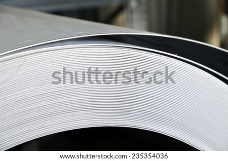 Close up of rolls metal material inside a industrial warehouse for production of sportive homemade muffler. - stock photo
