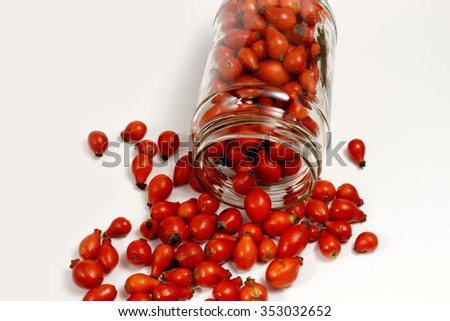 Close up of rose-hip berries and a jar with white background