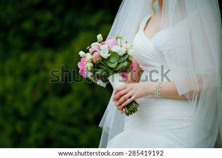 Close-up of roses wedding bouquet in a hands of a slim bride in a white wedding dress - stock photo