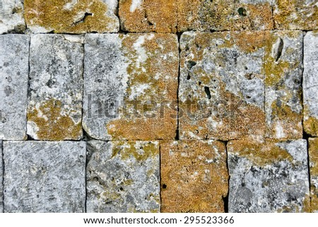 Close-up of rough, textured mossy stone wall  - stock photo
