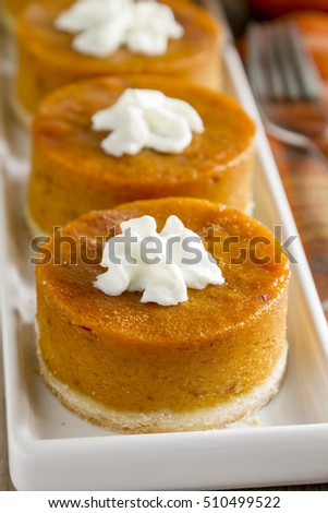 Close up of row of mini pumpkin pies with whipped cream sitting on white plate with orange napkin and fork