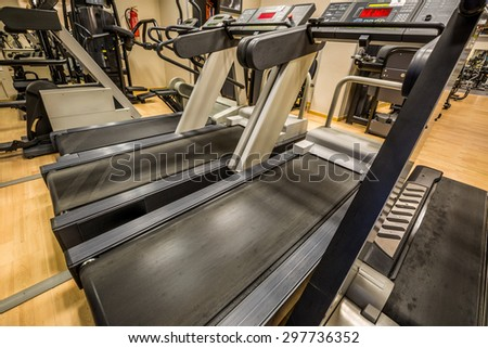 Close-up of row of treadmills in modern gym with parquet.
