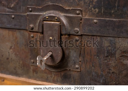 Close Up of Rusty Lock and Key Belonging to Antique Wooden Trunk with Weathered Wood - stock photo
