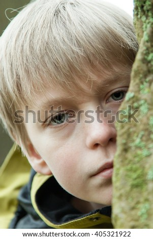 Close up of sad or scared single male child in coat peeking from behind large mossy rock