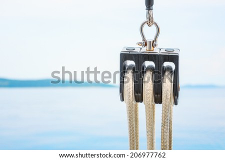 Close-up of sailing pulley, with sea and sky in the background - stock photo